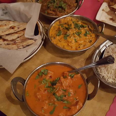An array of food here including chicken korma, eggplant baingan bharta. onion kulcha naan, and basmati rice.