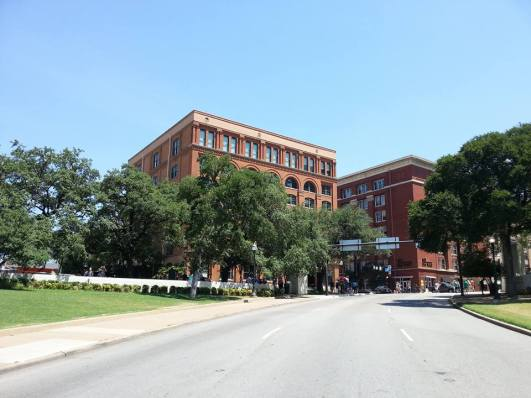 Standing at the site of the final shot that killed JFK in Dealey Plaza, while the School Book Depository looms in the background (Dallas, TX).